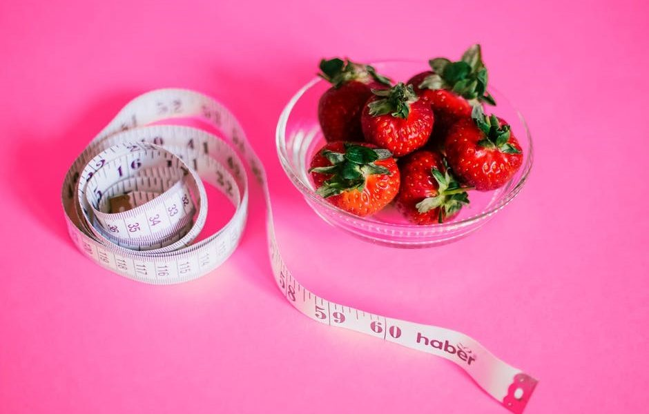 Nutrição e Dietética, Uma foto de fundo roda, com uma fita metrica e um pote de vidro com morangos